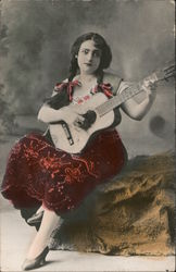 A Woman Sitting on a Rock Playing a Guitar