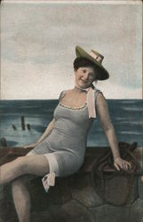 A woman relaxing in a bathing suit and hat Postcard