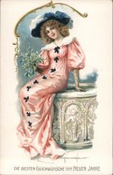 A woman smiling and dressed in a long pink dress with a blue hat. Postcard