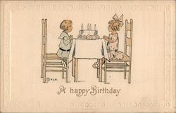 "Girl and boy seated at table with cake: ""A happy birthday"" Postcard"