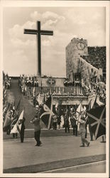 People bearing a variety of flags marching in front of a large Cross at Olympic Stadium in Berlin