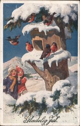 Two children in snow suits looking up into a snow covered tree looking at robins around a bird house Postcard