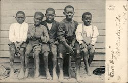 5 African American children sit on a bench outside a house