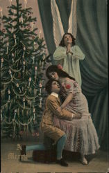 A Man and Woman Hugging in Front of a Christmas Tree and an Angel