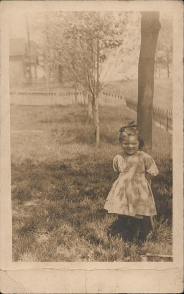 Little girl in a dress standing in front of a tree