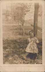 Little girl in a dress standing in front of a tree Postcard