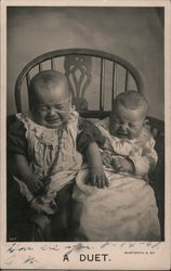 A Duet. Two babies sitting in a chair crying. Postcard