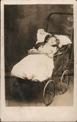Baby strapped in open baggy buggy, photo studio Postcard