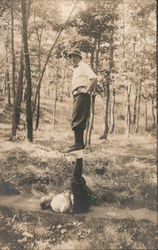 Two men doing acrobatic pose in forest Postcard