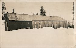 Large two story wood frame building in winter Postcard