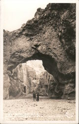 Couple standing below a natural stone arch Postcard