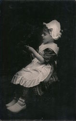 Young Dutch girl wearing apron, lace hat, clogs Postcard