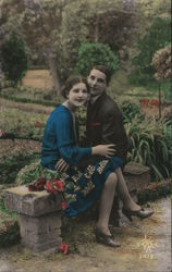 Young couple sitting on a bench in an French garden - in coor Postcard