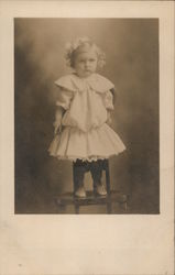 Little Girl in Dress Standing on Chair