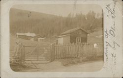 Wooden Homes Behind a Wooden Picket Fence and Gate Postcard