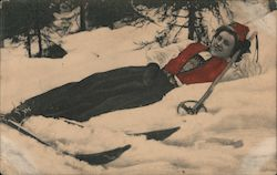 Female skier laying in snow Postcard