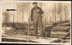 Man in Insulated Overalls in Front of Log Pile Postcard