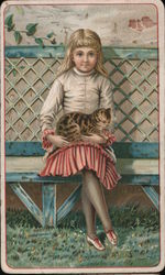 Girl in red and white dress holding a cat