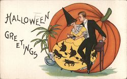 Halloween Greetings - Man with woman dressed in witch garb sitting in front of a huge pumpkin