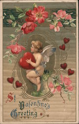 Cupid holding a heart sitting among pink flowers