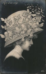 Woman in a hat that has winged men on it Postcard
