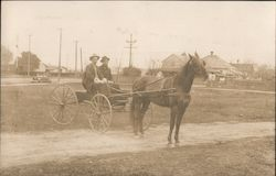 Two Men In a Wagon Pulled by a Horse Town in Background