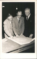 Three Men Looking Over Blueprints