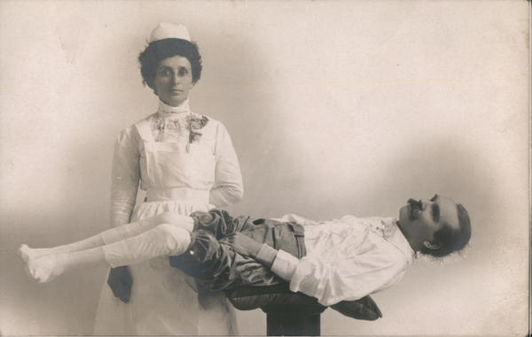 A Nurse Standing Next to a Man who is Lying Down Frank Worden