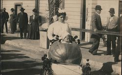 A Woman Pushing a Child in a Large Pumpkin Postcard
