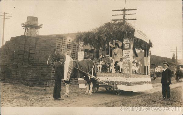 Parade float horse drawn with bunting and signs advertising a store. Children on float Fortuna California