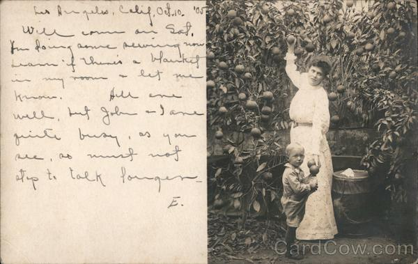 Woman and Child in a garden picking Oranges Los Angeles California
