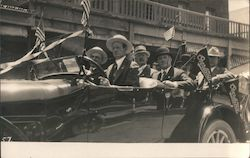 Men driving new car in Parade US Flags, Overland banners Postcard