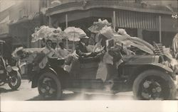 Women with parasols in open car decorated with bunting and US Flag Postcard