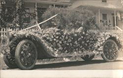 A Man and Woman in a Car That is Covered By Flowers Postcard