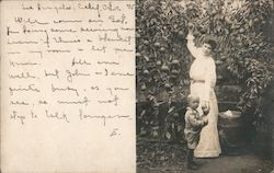 Woman and Child in a garden picking Oranges Postcard