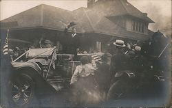 Theodore Roosevelt tipping hat in back of car with crowd of people