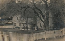 Group of people in a fenced in yard Postcard