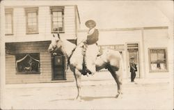 Cowboy on horse posed on main street Postcard