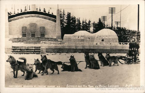 Seppala and His Team of Racing Siberians - Dog Sled team and driver, with building and igloo in the background