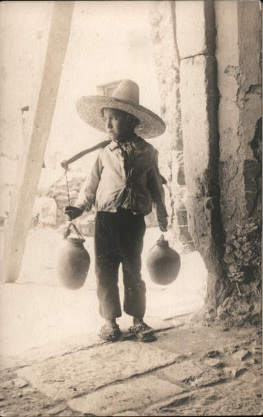 Mexican boy with water jugs Mexico
