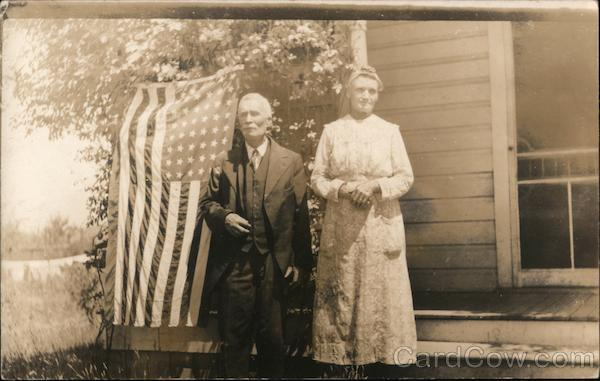 Man and Woman standing by U.S. Flag by porch of house