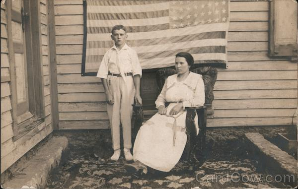 Young Boy and Woman behind Upside Down American Flag