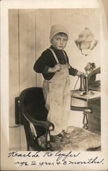 Boy in overalls standing on chair holding telephone Postcard