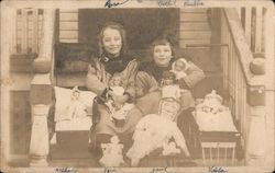Two girls with several of their dolls