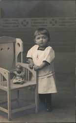 Child photo with doll in chair