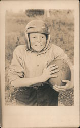 Boy wearing football helmet and holding football Postcard