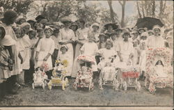 Group of people dressed in white, and girls with flowered doll strollers