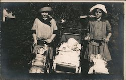 Two girls, baby in stroller, two doll strollers