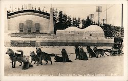 Seppala and His Team of Racing Siberians - Dog Sled team and driver, with building and igloo in the background Postcard