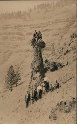 People posing with tall rock formation on side of mountain Postcard